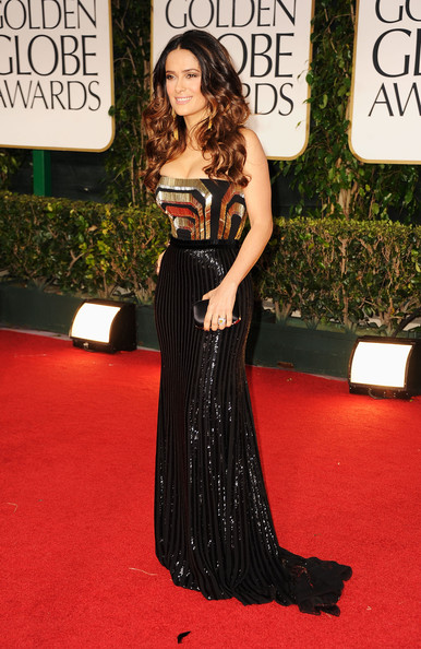 Presenter Salma Hayek-Pinault wore a Gucci Art Deco strapless evening gown with a black satin evening clutch. The dress features a graphic bustier embroidered with antique gold and silver glass bugle beads, thin beaded black belt and a fully embroidered liquid skirt of vertical lines of glass beads and black satin peep toe evening shoes.